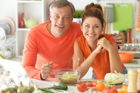Happy married couple cooking together on kitchen