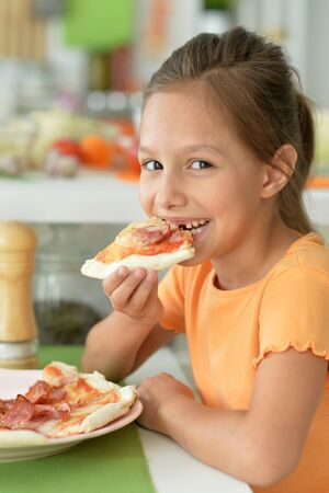 Portrait of cute girl eating pizza and posing at home
