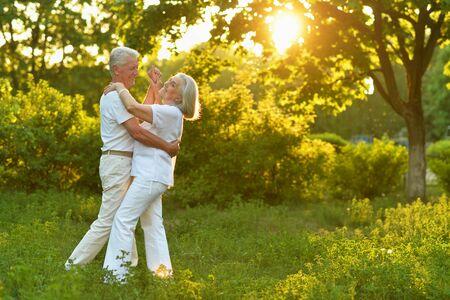 Portrait of happy beautiful senior couple dancing in summer park Standard-Bild - 130089793