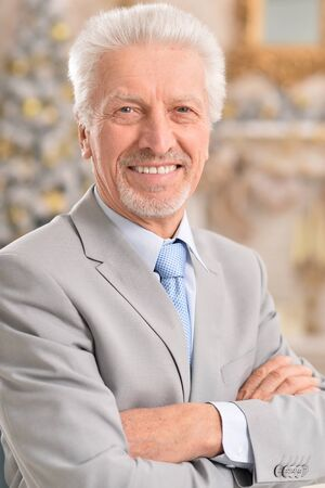 Senior businessman posing on blurred festive background