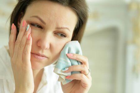 Beautiful young crying woman posing at home