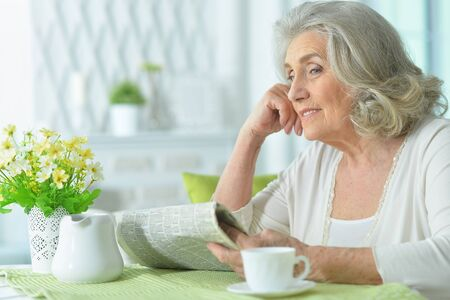 Senior woman reading newspaper and posing at home