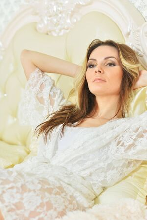 Portrait of young woman lying on vintage bed at home