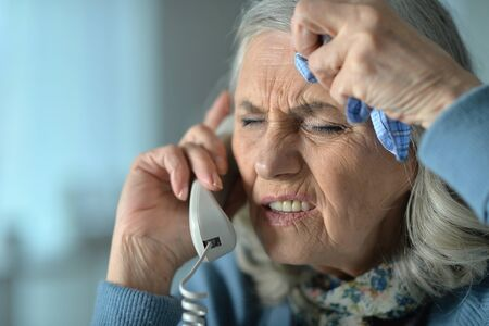 Portrait of an upset senior woman calling doctor Stok Fotoğraf
