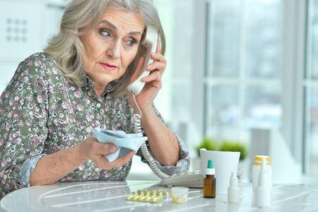 Portrait of ill senior woman calling doctor