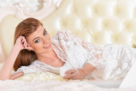 Beautiful young woman on bed with laptop at home