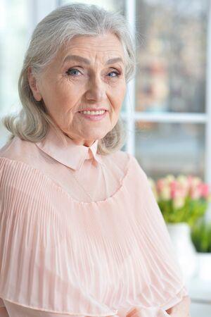 Happy smilling senior woman posing at home