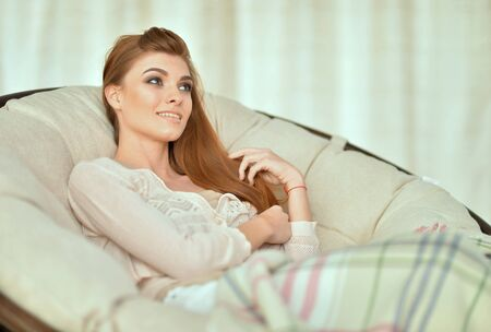 Beautiful young woman relaxing in chair at home