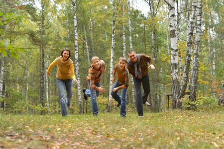 Portrait of family of four having fun in autumn forest
