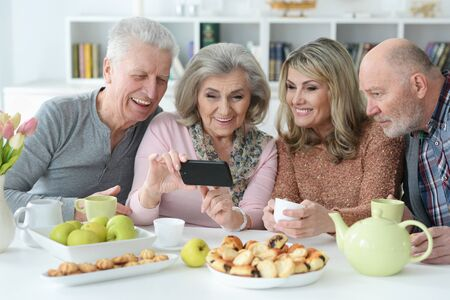 Two senior couples using smartphone during morning tea Stok Fotoğraf
