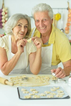 Portrait of senior couple baking in the kitchen at home Stock Photo