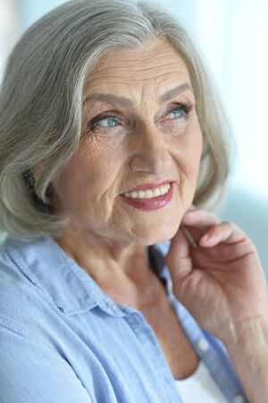 Happy senior woman at home with flowers Stock Photo