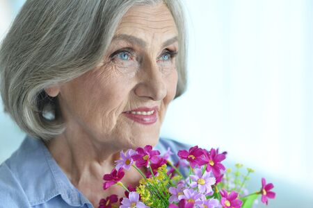 Happy senior woman at home with flowers Stok Fotoğraf
