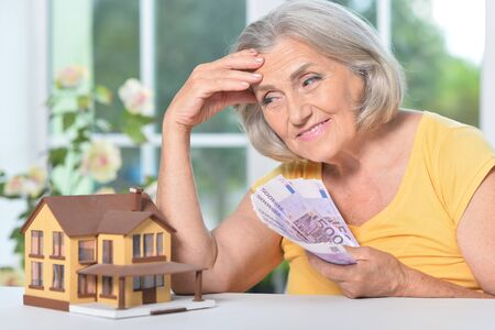 Portrait of elderly woman with euro bills and house