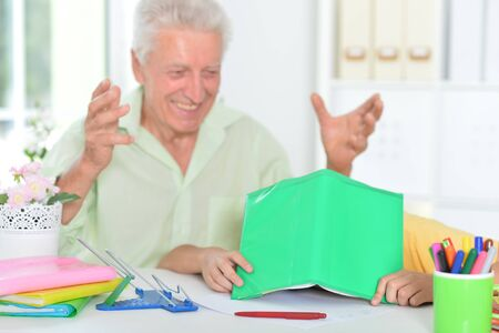 Portrait of grandfather with her grandson doing homework at home Stok Fotoğraf