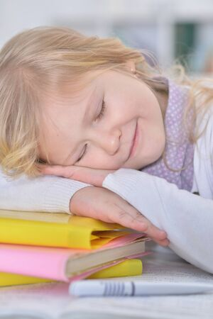 Close up portrait of cute schoolgirl sleeping on table
