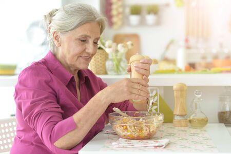 Portrait of cute senior woman chef portrait at kitchen
