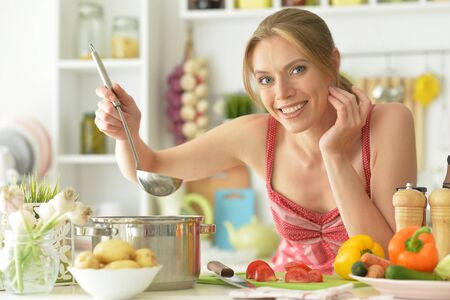 Portrait of a beautiful young woman cooking in kitchen