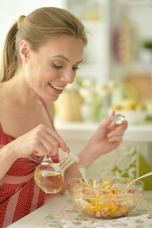 Portrait of beautiful young woman cooking in kitchen