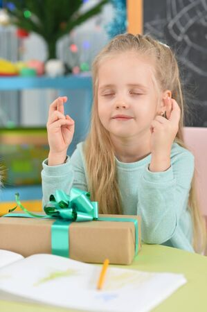 Close up portrait of cute girl sitting at table with gift