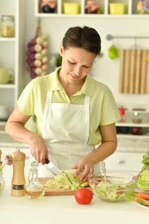 Close up portrait of beautiful young woman making salad in kitchen