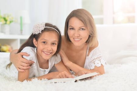 little cute girl with mother reading book Imagens