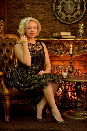 Young woman posing while sitting on a vintage armchair Imagens - 132024680