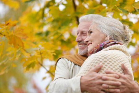 Portrait of beautiful senior couple hugging in the autumn park