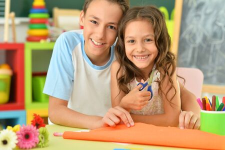 Cute brother and sister gluing and cutting colorful paper