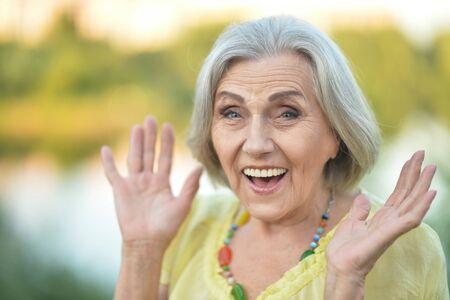 Close up portrait of smiling surprised senior beautiful woman posing