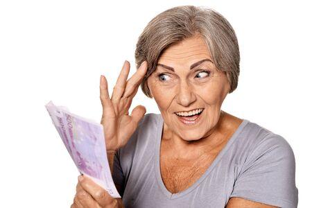 Portrait of happy elderly woman with euros