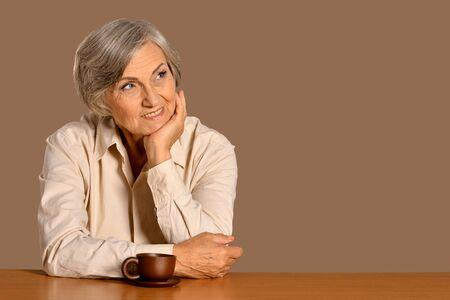 portrait of happy senior woman at table Stock Photo