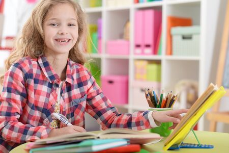 Nettes jugendlich Mädchen, das Hausaufgaben in ihrem Zimmer macht
