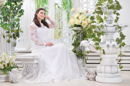 portrait of young beautiful bride in white dress posing