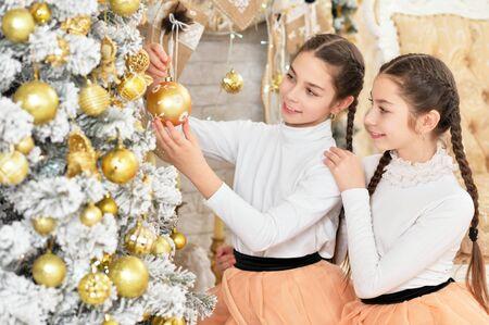 Portrait of ute girls decorating Christmas tree