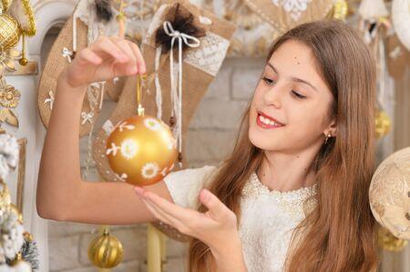 Retrato de niña feliz decorar el árbol de Navidad