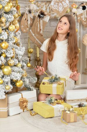 Portrait of happy teenage girl sitting with gifts
