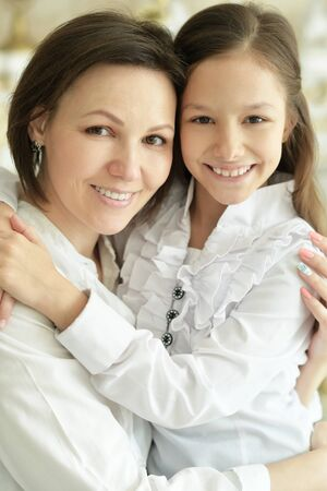Beautiful young mother and cute little daughter posing