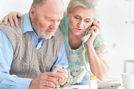 Ill senior couple at home calling doctor Stock Photo