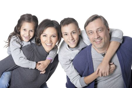 Portrait of happy smiling family of four posing together on white