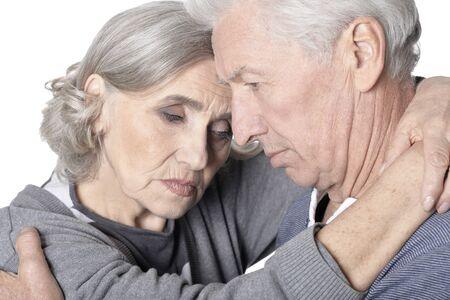 Close up portrait of sad senior couple isolated on white background