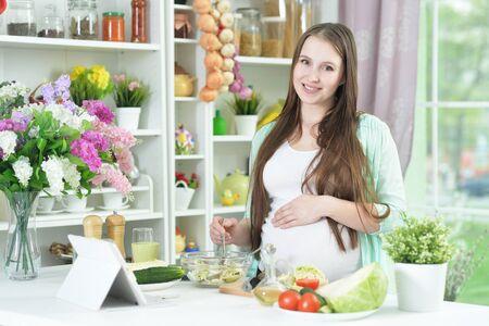 Hermosa joven embarazada cocinando en la cocina