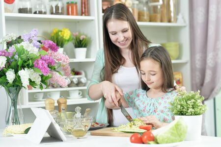 Smiling pregnant mother and daughter cooking together at kitchen Stock Photo