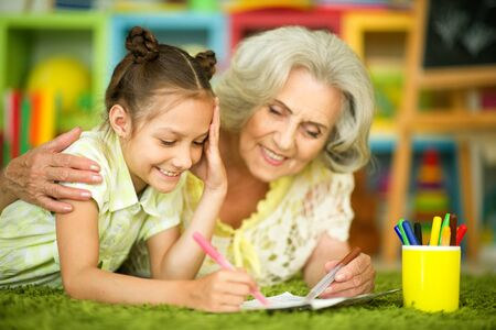 Portrait of grandmother and granddaughter drawing together Stock Photo - 136988099