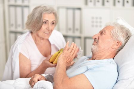 Senior man portrait in hospital with caring wife bringing bananas