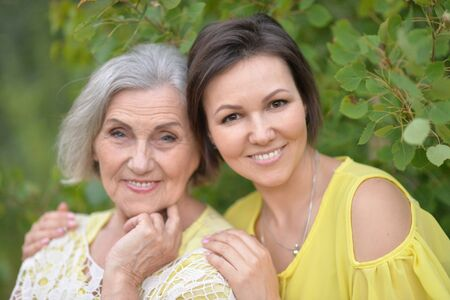 Smiling senior woman with adult daughter in autumnal park