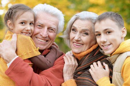 Happy grandfather, grandmother and grandchildren in park