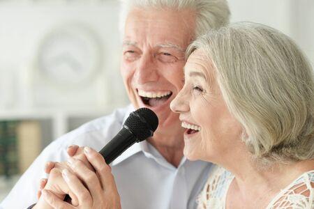 Close up portrait of senior couple singing karaoke