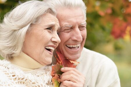 Portrait of beautiful senior couple with leaves in the park 版權商用圖片