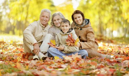Cute happy family relaxing in autumn forest